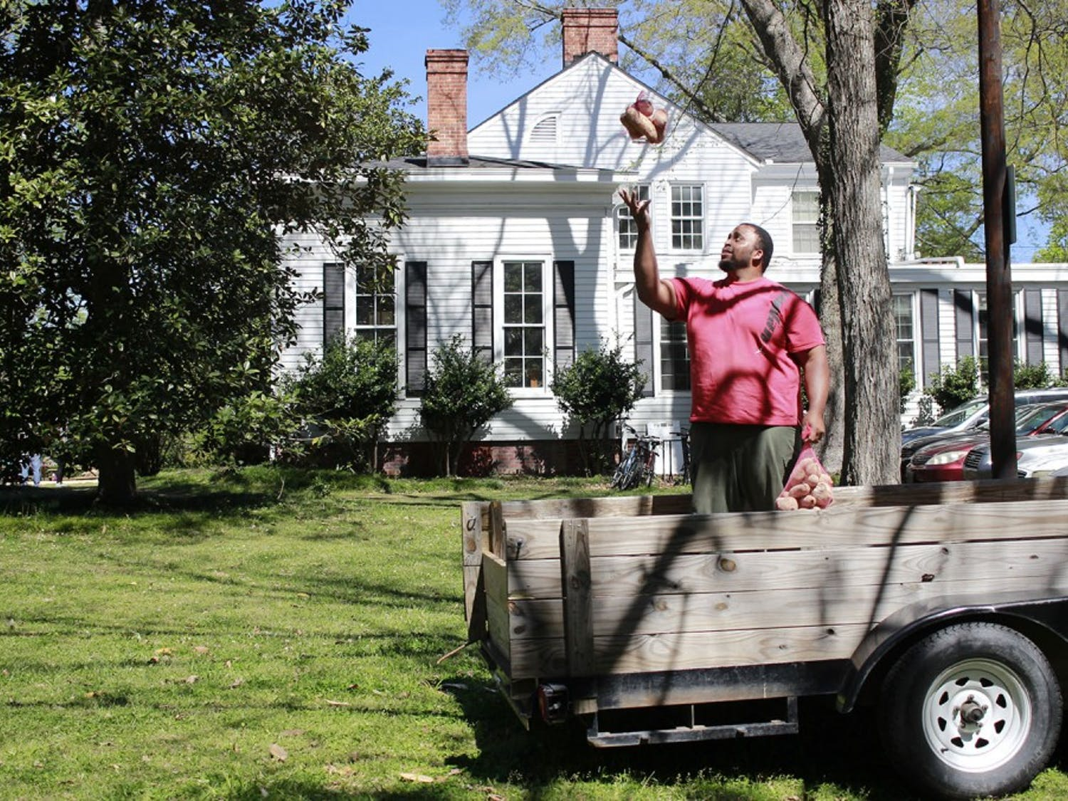 Jason Brown, a former UNC football player, tosses a sack of sweet potatoes into the air behind the UNC Study Center on Saturday. Brown, who left the NFL to become a farmer, donated 20,000 pounds of sweet potatoes to food banks and church programs across North Carolina. The potatoes were bagged up by local volunteers to be shipped out on Saturday.