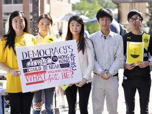 From left to right, Sam Lin, Kathleen Cheng, Christie Leung, Tim Kang, and Kiko Wong stand together to support Hong Kong, sponsored by the Asian Students Association at UNC. Christie and Kiko are students from Hong Kong studying at UNC through the GLOBE program, Sam and Tim are students at UNC and members of the Asian Students Association, and Kathleen graduated from UNC with the Class of 2014.