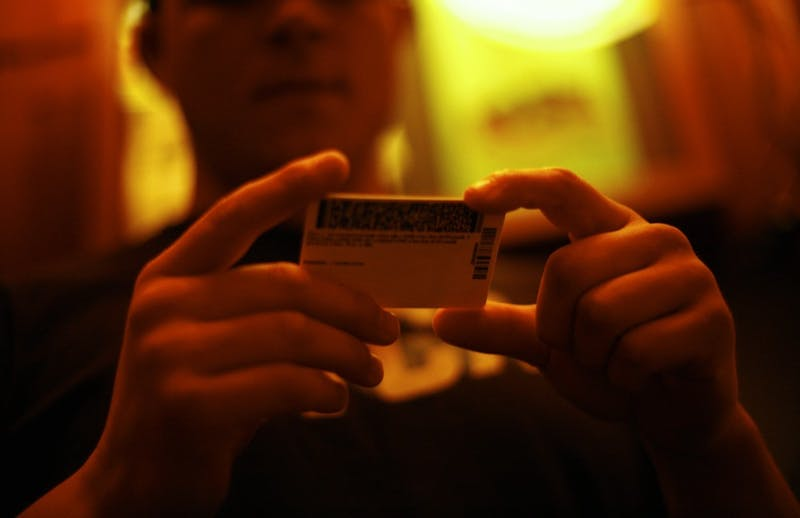 Andrew Phillips, a senior EXSS major from Canton, Ohio, examines (my) ID at Goodfellows on Franklin St. The bar-back has worked at the bar for almost two years and says he can pretty quickly tell the difference between a real and a fake ID. Holograms and the numbers on the cards are the first indicators he looks at to see if they're real.