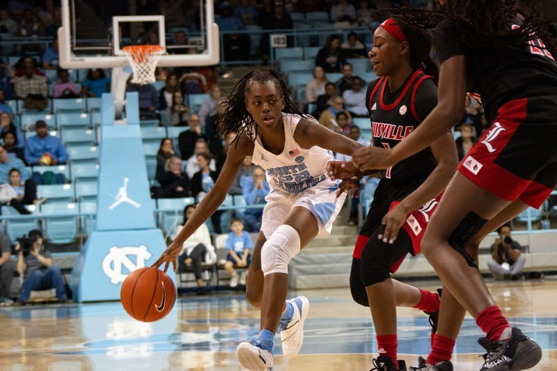 Senior guard Shayla Bennett (22) dodges opposing players in the game against Louisville at Carmichael Arena on Sunday, Jan. 19, 2020. UNC lost 67-74.