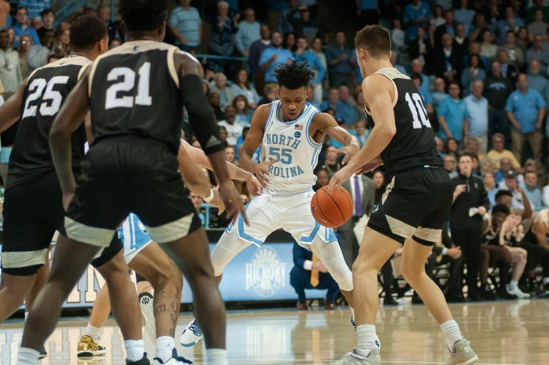 UNC's graduate guard Christain Keeling (55) attempts to gain possession of the ball during a game against Wofford on Sunday, Dec. 15th, 2019 at Carmichael Arena. This is the first regular-season game the Tar Heels have played in Carmichael since 1986.  UNC fell to Wofford 64-68, marking UNC's third consecutive loss.