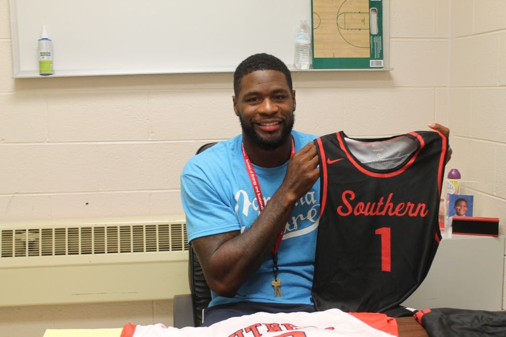 <p>Southern Durham men's basketball head coach David Noel poses with a team jersey. Noel, who won a national championship with the UNC basketball team in 2005, returned to his former high school as a coach in late August.</p>