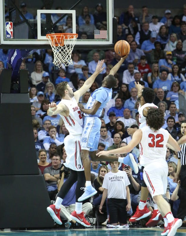 Guard Brandon Robinson (4) twists around a Davidson defender for a layup on Friday in the Spectrum Center in Charlotte.