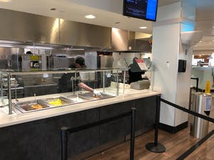 A Carolina Dining Services worker attends to food in the Chase Dining Hall on Tuesday, March 17, 2020.