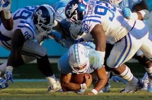 UNC quarterback Chazz Surratt(12) gets sacked by Duke players on Saturday.