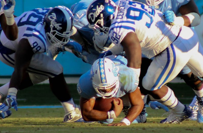 UNC quarterback Chazz Surratt(12) gets sacked by Duke players on Saturday.