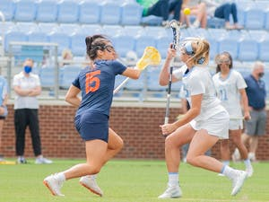 UNC senior midfielder Ally Mastroianni (12) fights for the ball at tip at the game against Virginia on Sunday Apr. 18, 2021 at the Dorrance Field. UNC won 15-4.