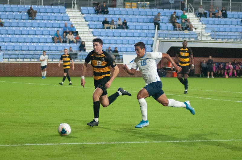 First-year UNC forward Jonathan Jimenez (16) and sophomore Appalachian State University defender Mason Robicheaux (12) chase the ball on Tuesday, Oct. 29, 2019. UNC lost to Appalachian State University 1-0 on a penalty kick.