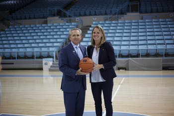 Courtney Banghart, the newly hired UNC women's basketball head coach, poses with athletic director Bubba Cunningham at a small press conference in Carmichael Arena about her hopes for the program on May 1, 2019.