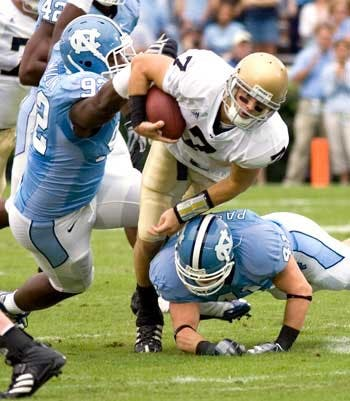 "UNC?s E.J. Wilson (92) and Mark Paschal (41) work on a takedown of Notre Dame QB Jimmy Clausen"" who was sacked four times on the day."