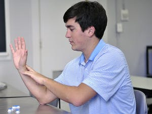 Jeff Powell, a senior biomedical engineering major and design chair of the UNC-Chapel Hill Biomedical Engineering Club, made a prosthetic arm for 7-year-old Holden Mora with 3-D printing technology. Powell uses the three model fingers on the table to explain how each part of the hand is made.