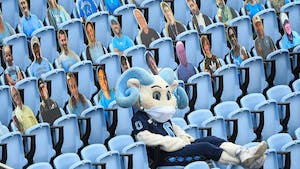 UNC mascot RJ lounges in the stands of Kenan Memorial Stadium alongside fan cardboard cutouts during a game against Virginia Tech on Saturday, Oct. 10, 2020. UNC beat Virginia Tech 56-45.