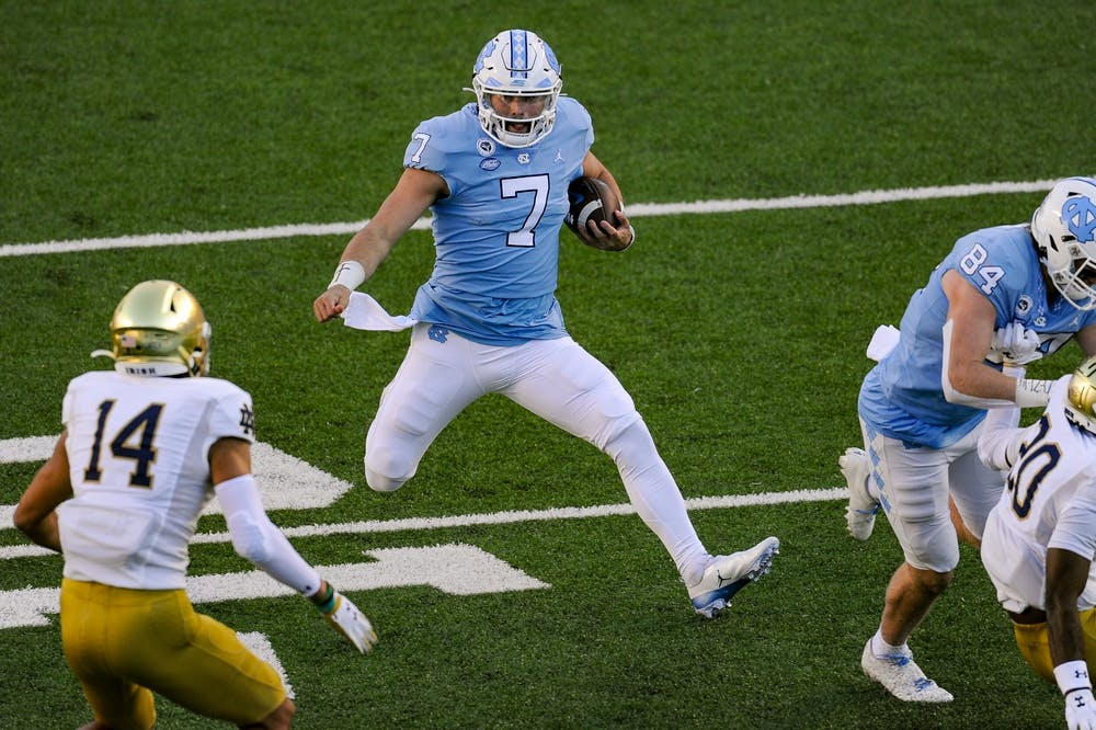 <p>UNC's sophomore quarterback Sam Howell (7) runs the ball during a game against Notre Dame in Kenan Memorial Stadium on Friday, Nov. 27, 2020. Notre Dame beat UNC 31-17.</p>