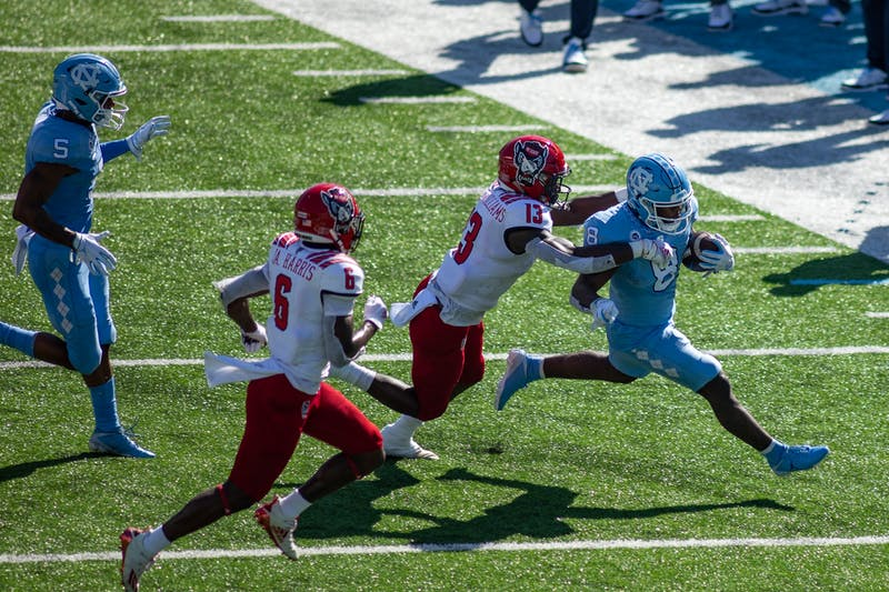UNC senior running back Michael Carter (8) rushes in Kenan Stadium Oct. 24, 2020. The Tar Heels beat the Wolfpack 48-21.