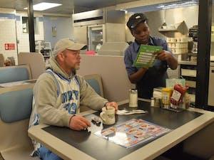 Waffle House server Katherine Burgin takes customer Tim Pruitt's order at Waffle House on Franklin St.