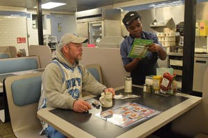 Waffle House server Katherine Burgin takes customer Tim Pruitt's order at Waffle House on Franklin St.