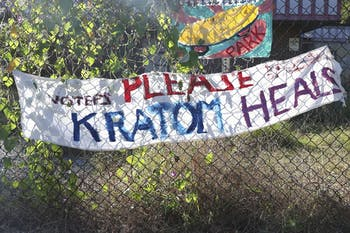 A banner calling for voters to not outlaw kratomhangs on a fence on the cornerN. Greensboro St.and E. Weaver St.