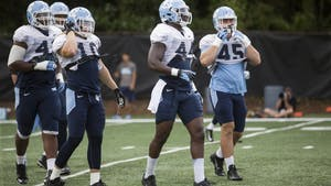 Tarheel Junior Gnonkonde, center, lines up to run through a play during practice on Tuesday, August 25, 2015.