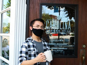On-Duty Manager, Victor Yax, poses in front of Carolina Coffee Shop.
