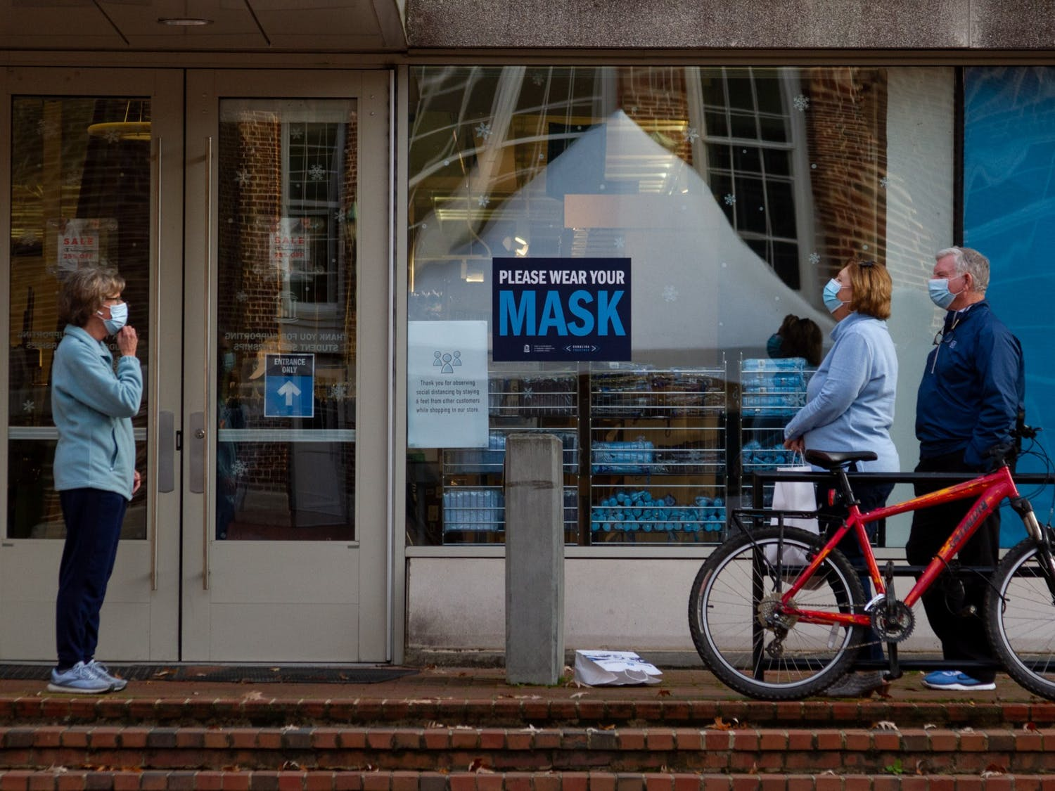 People converse while socially-distanced and wearing masks outside of the Student Stores on Saturday, Nov. 14, 2020.