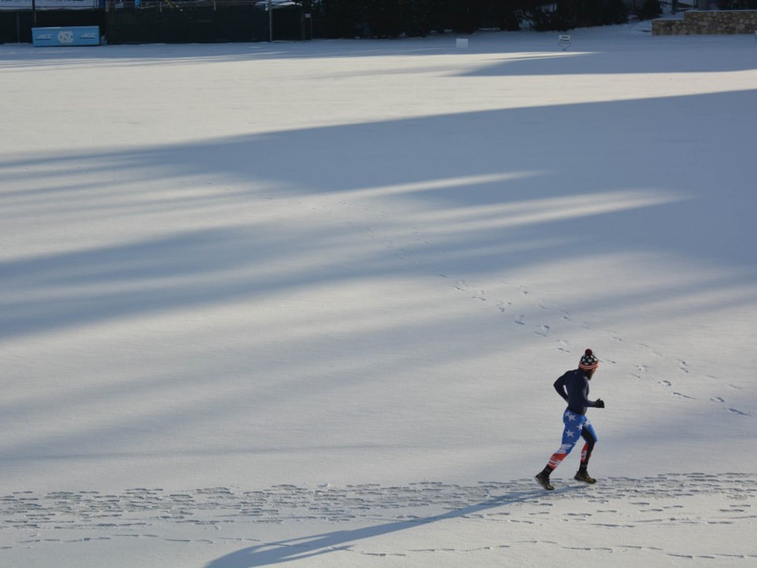 A runner circles the snow covered track on Fetzer Field.
