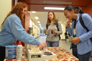 Maddy Munoz, a Loco Cocoa organizer, serves hot chocolate to UNC students Eileen Yang and Parker Novack at the Student Union on Tuesday morning.