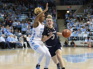 Redshirt senior guard Paris Kea (22) protects the rim against Notre Dame senior guard Marina Mabrey (3) in a UNC upset in Carmichael Arena on Jan. 27, 2019. Kea finished the game with 30 points, 10 assists and 3 rebounds. UNC wins 78-73.