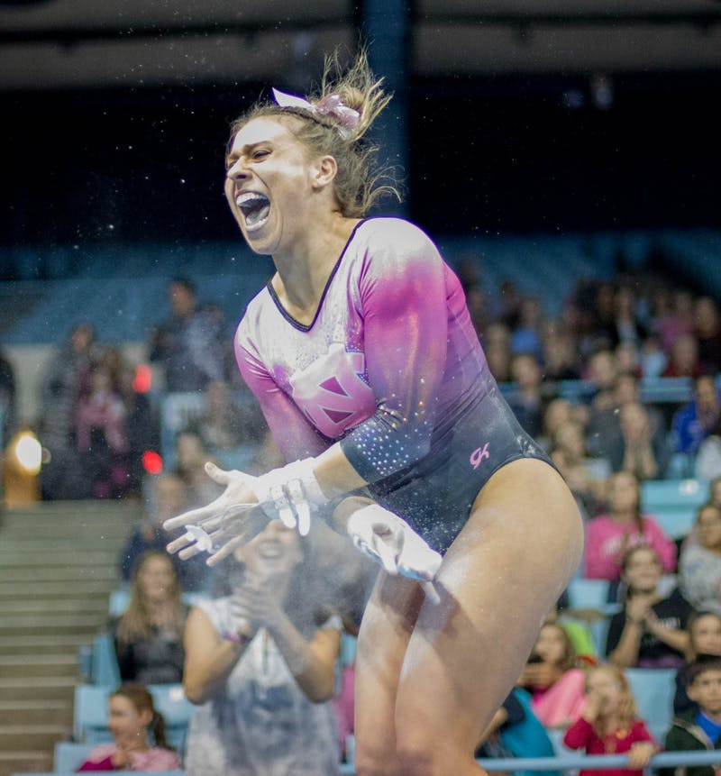 Megan Ruzicka celebrates after completing a routine on the uneven bars during home opener and annual Women's Day and Pink Meet against Oklahoma and Ball State on Saturday, Jan. 19, 2019. UNC placed second behind Oklahoma.