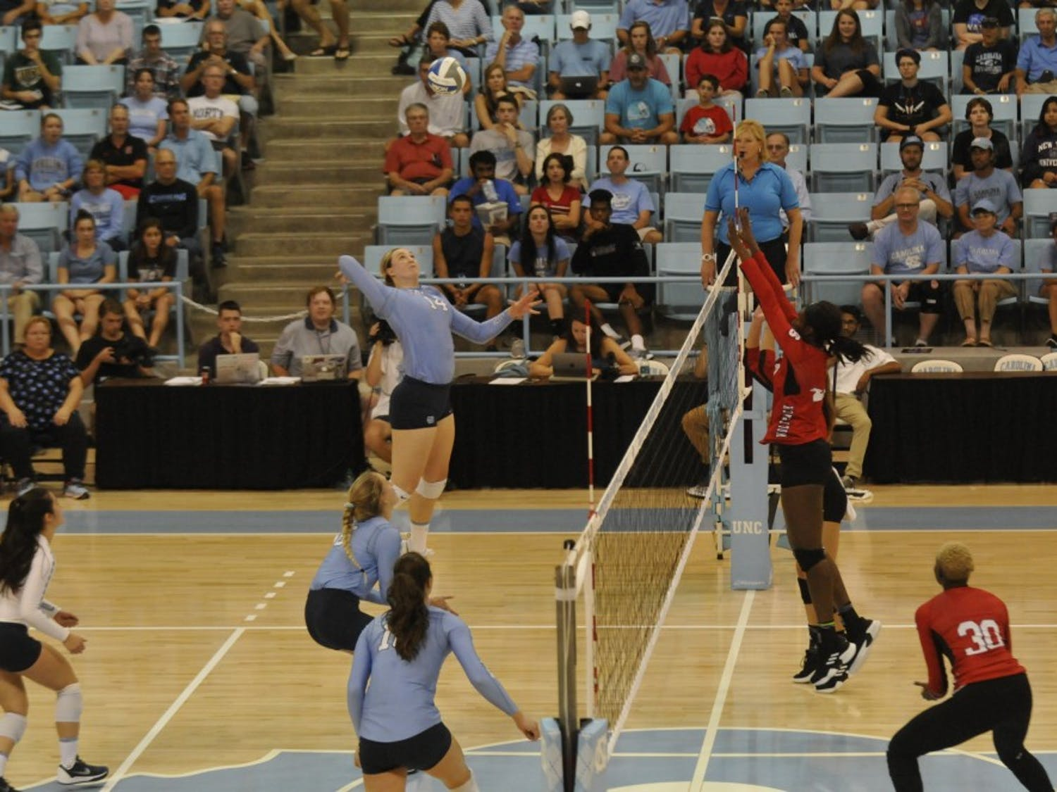 Senior outside hitter Madison Laufenberg (14) spikes the ball towards her NC State opponents on Wednesday, Sept. 26 in Carmichael Arena.