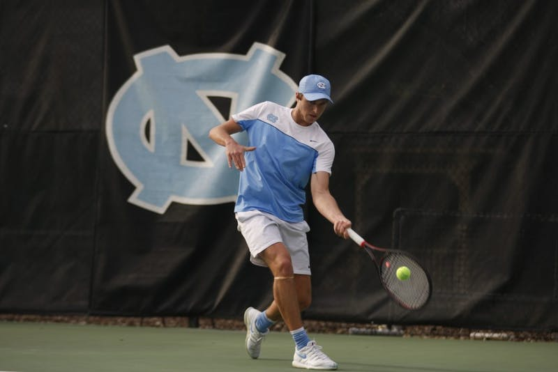 First-year Brian Cernoch, undeclared major, prepares to hit the tennis ball as he plays for the UNC men's tennis team against Duke on Thursday, Feb. 28, 2019 at the Cone-Kenfield Center. UNC won 4-1. Cernoch won his singles match.