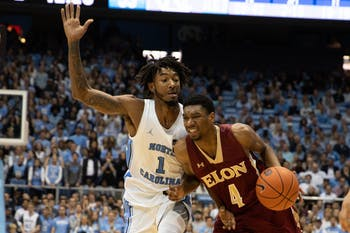 Elon graduate forward Marcus Sheffield II (4) makes a drive past sophomore guard Leaky Black (1) during a game in the Dean Smith Center on Wednesday, Nov. 20, 2019. The Tar Heels beat the Phoenixes 75-61.