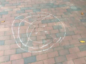 """Chalk messages around campus depict the symbol of Islam with an """"X"""" over it."""