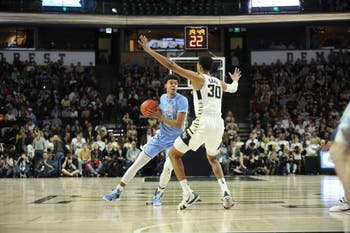 Wake Forest sophomore center Olivier Sarr (30) attempts to block UNC graduate guard Cam Johnson (13) during No. 8 UNC's 95-57 win over Wake Forest on Saturday, Feb. 16, 2019 at Lawrence Joel Veterans Memorial Coliseum. Johnson scored 27 points for the Tar Heels.