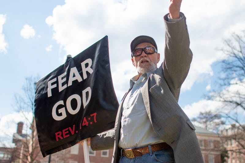 """Gary Birdsong, the """"Pit Preacher,"""" holds up his sign as he preaches at Polk Place on Monday, March 18, 2019."""