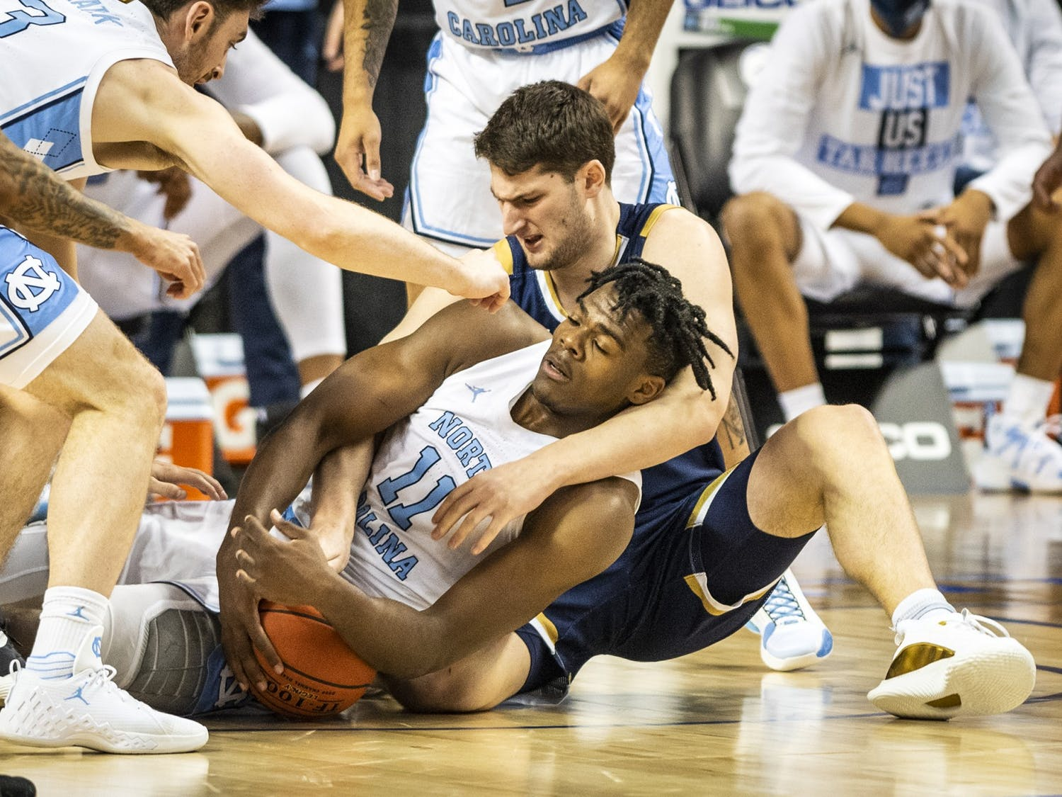 Carolina's Day'Ron Sharpe (11) battles Notre Dame's Matt Zona (25) for a loose ball on Wednesday, March 10, 2021 in Greensboro, N.C. Photo courtesy of Andrew Dye/Winston-Salem Journal