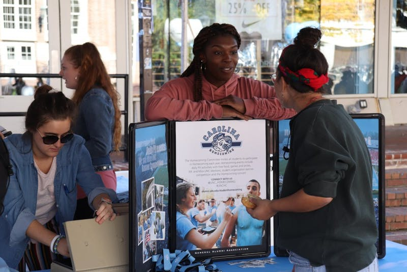 Marketing co-chair Valerie Evivie, a junior health policy and management major, of the UNC-Chapel Hill Homecoming Committee gives students information on Homecoming 2018 in the Pit on Tuesday, Oct. 30, 2018.