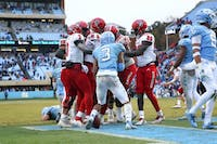 Linebacker Dominique Ross (3) plunges into a sea of NC State's offense to spark the post-game brawl on Saturday, Nov. 24, 2018 in Kenan Memorial Stadium.