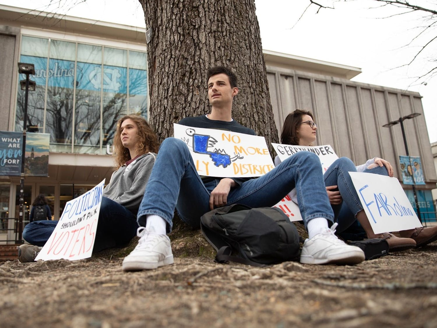 "(From left) Max Kurzman, Patrick Clinch, Annie Evans sit in the pit on Monday, Mar. 2, 2020 for FAIRolina: UNC's Weekly Voting Rights Protest. ""We're mad at the state of voting rights in North Carolina,"" Evans said. ""We're out here every Monday from 12 to 1 protesting a different voting rights issue each week."""