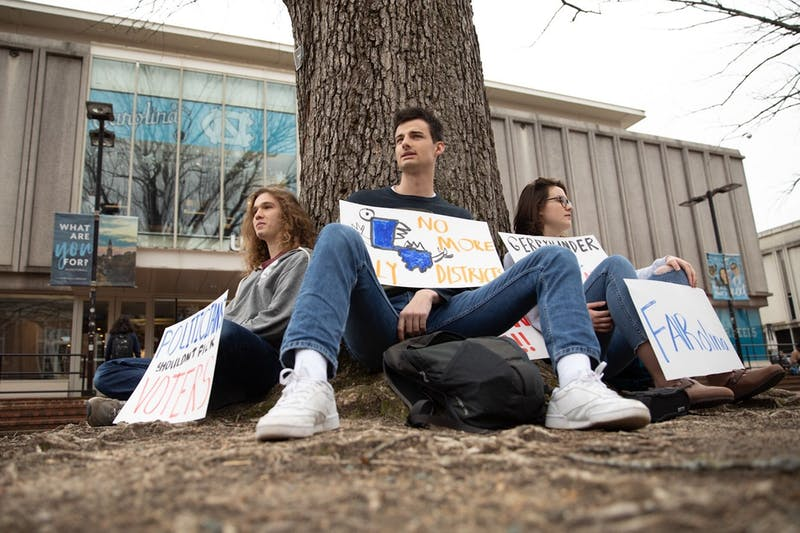 """(From left) Max Kurzman, Patrick Clinch, Annie Evans sit in the pit on Monday, Mar. 2, 2020 for FAIRolina: UNC's Weekly Voting Rights Protest. """"We're mad at the state of voting rights in North Carolina,"""" Evans said. """"We're out here every Monday from 12 to 1 protesting a different voting rights issue each week."""""""