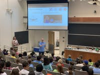 Stefan Jeglinski demonstrating an experiment using gravity to a room full of students. The demonstration was just one of many to show physical examples of science concepts the students learned about in class.