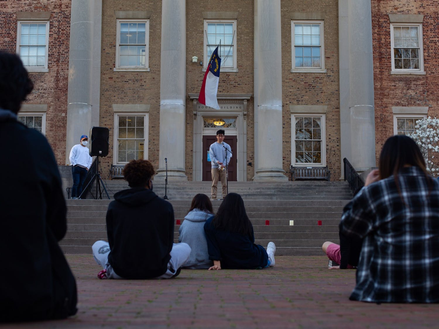 Students and alumni sit together to listen to other members of Chapel HIll community in honor of the 8 lives lost in Atlanta on March 16, 2021.