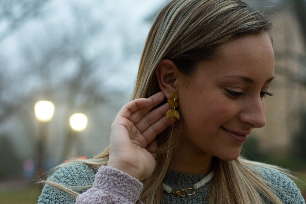 <p>Anna Jordan, '22, the owner of AnnaBanana Jewelry, shows off a pair of earrings from her newest collection on February 15, 2021 at McCorkle Place. Jordan used to make faux leather pieces, she said, but now the business focuses on clay and resin jewelry.</p>