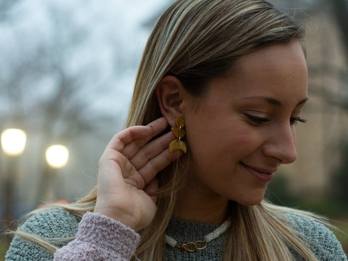 Anna Jordan, '22, the owner of AnnaBanana Jewelry, shows off a pair of earrings from her newest collection on February 15, 2021 at McCorkle Place. Jordan used to make faux leather pieces, she said, but now the business focuses on clay and resin jewelry.