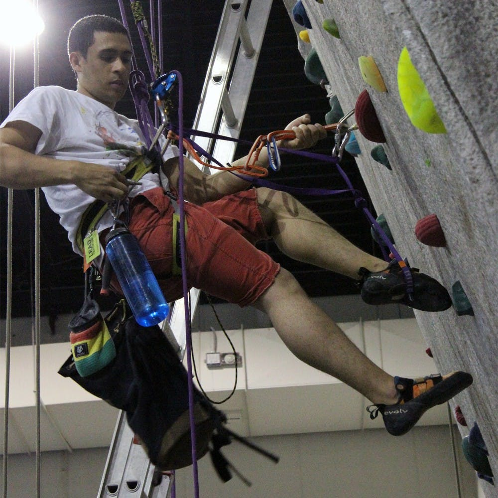 Christian Reyes sets up for the Tar Heel Top Out in Fetzer Gym C on Thursday afternoon. UNC Chapel Hill is hosting the Tar Heel Top Out, a top rope climbing competition, on Saturday. The event is part of the 5th annual Eastern Edge Climbing series.