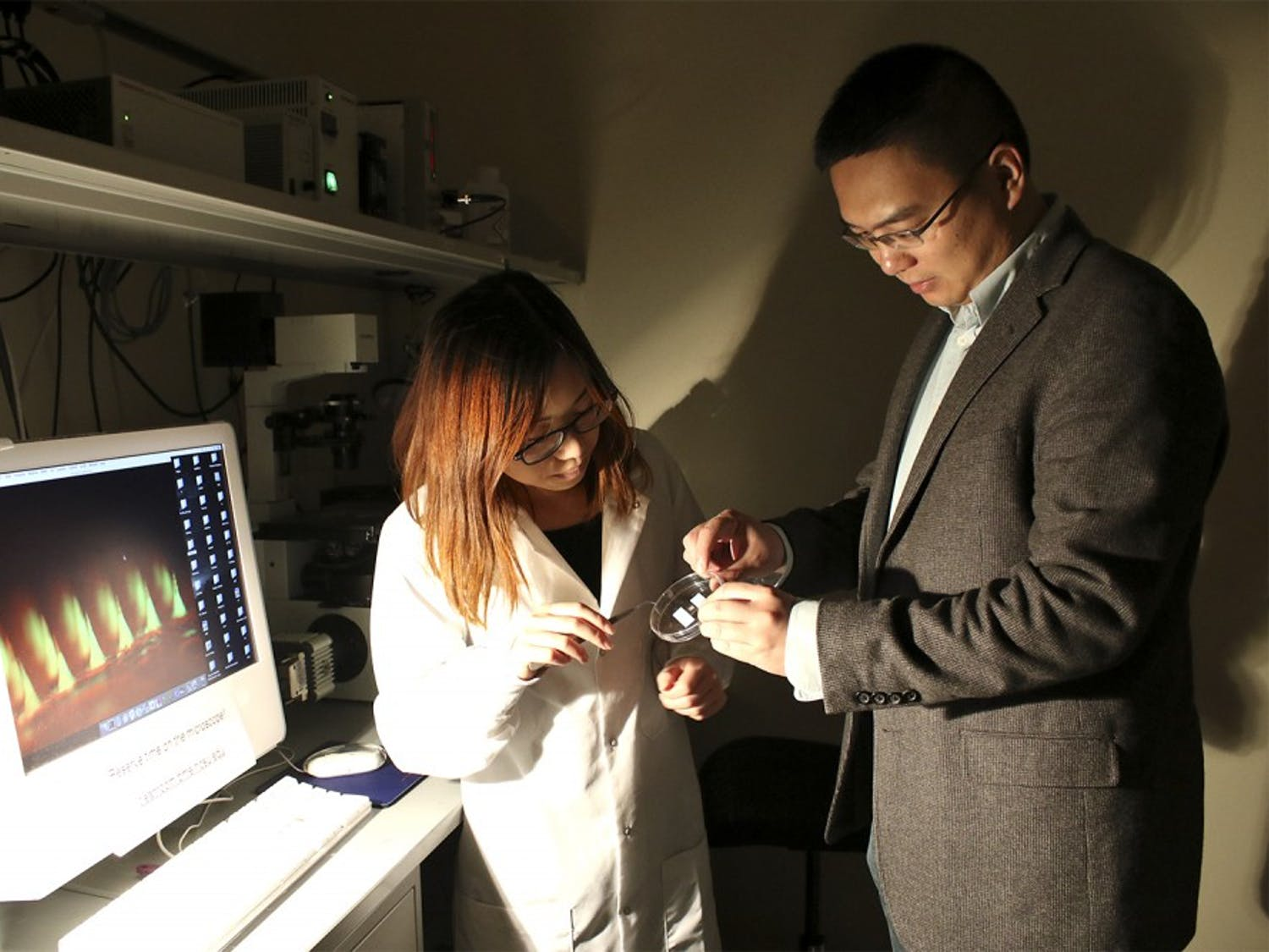 Zhen Gu (right) and Ph.D. student Yanqi Ye demonstrate the equipment used to take Gu's award-winning photo of the insulin patch the lab developed.
