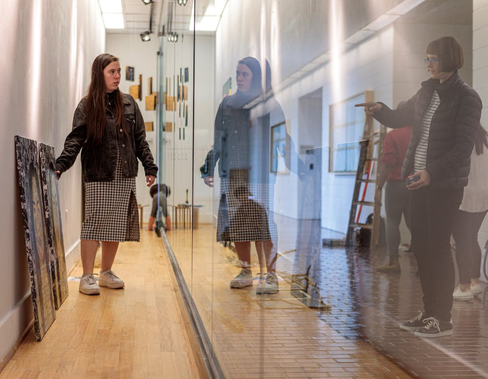 """<p>Senior studio art major Peri Law (left) and Professor Gesche Würfel decide where to place work within the gallery as they install the """"Present"""" art show in the Hanes Art Center on Thursday, Nov. 7, 2019.</p>"""
