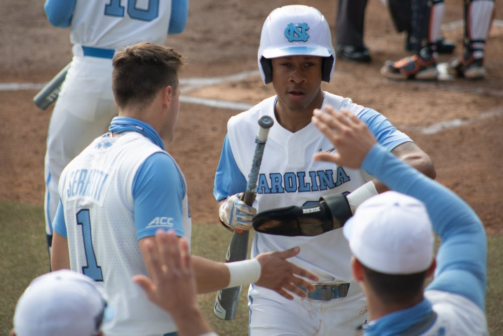 <p>Sophomore outfielder Justice Thompson (20) gets high fives from teammates after stealing home against University of Virginia on Saturday, Feb. 27, 2021. The Tar Heels beat the Cavaliers 2-1.</p>