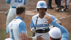 Sophomore outfielder Justice Thompson (20) gets high fives from teammates after stealing home against University of Virginia on Saturday, Feb. 27, 2021. The Tar Heels beat the Cavaliers 2-1.