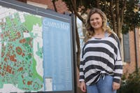 Kamryn Sain, a legacy student, smiles by a UNC campus map on Wednesday, Feb. 13, 2019. Both of Sain's parents attended UNC.