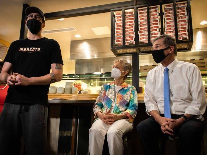 Gabe Barker, the owner and chef of Pizzeria Mercato in Carrboro, speaks Thursday after the restaurant implemented a vaccination requirement. Rep. Verla Insko and Gov. Roy Cooper look on.